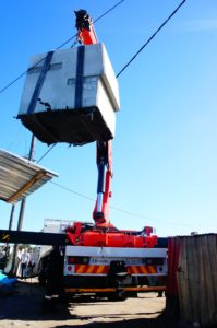 The crane hard at work, lifting the concrete installation well above all roofs, but careful not to hit any overhead electrical lines!