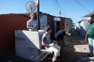 Mandela Day volunteer, Andrew stands in the 'pot' section to tighten the bolts, while designer Sebastian and community leader Billy test the stability of the attached bench.