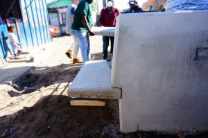 Side view of the bench, while in the background, community members carry the second piece of the bench into position.