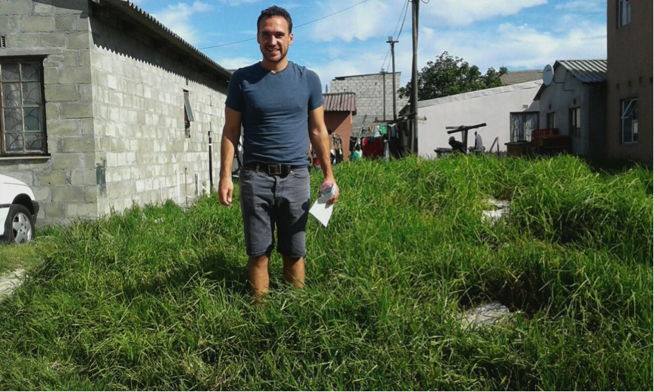 Nick demonstrating how overgrown grass and litter results in the loss of valuable land space, as well as a physical and social devaluation of the neighbourhood.